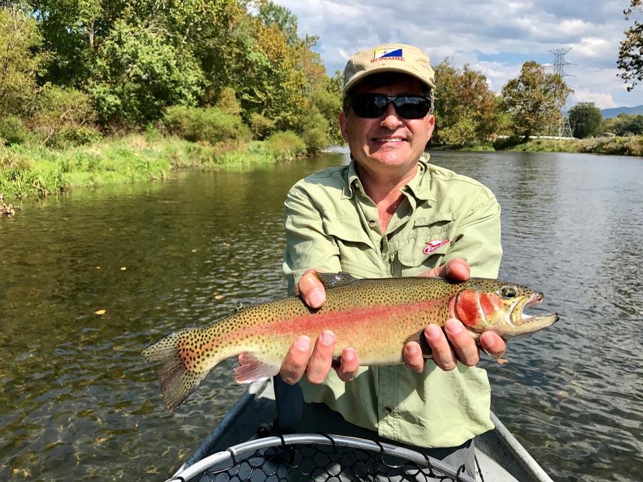 Man Wearing Hat and Green Shirt Holding Fish