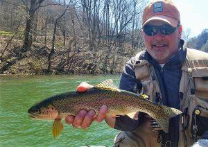 Man in Orange Hat Holding a Fish