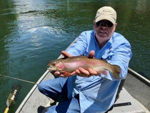 Older Gentleman in Blue Holding Fish