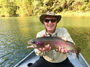 Man Smiling and Holding Rainbow Trout